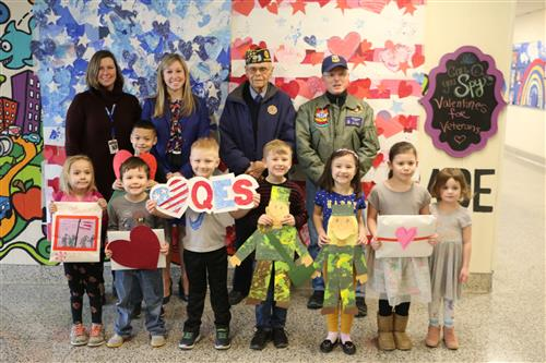Students and administrators presenting valentines to veterans