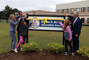 Representatives cut the ribbon on the new WHBI sign
