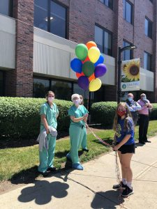 Student giving balloons to nurses