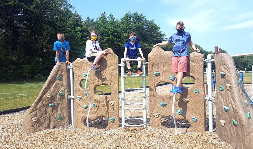 Four masked students pose on playground equipment