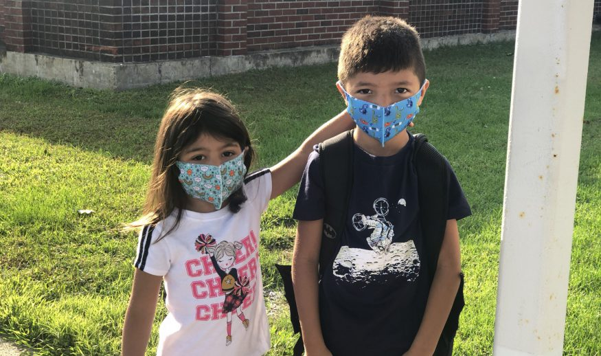 A masked QES student poses with his masked sister