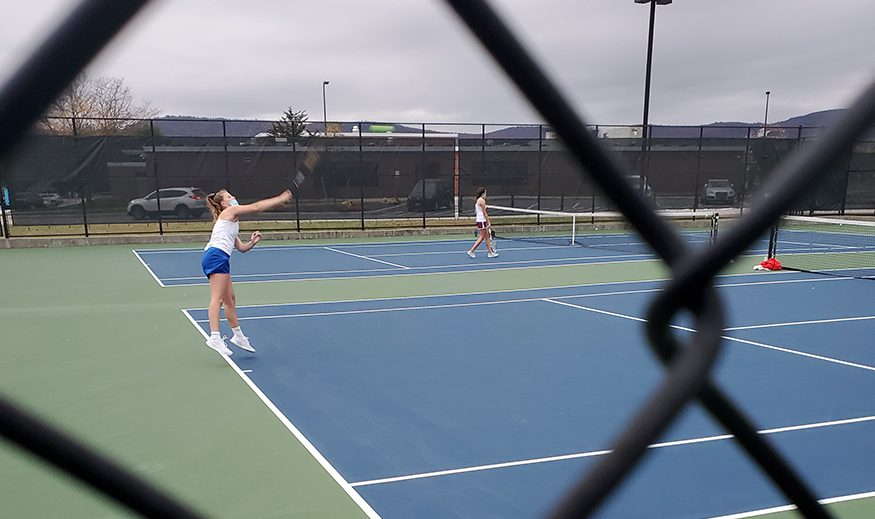 An action shot of a tennis player through the chain link fence