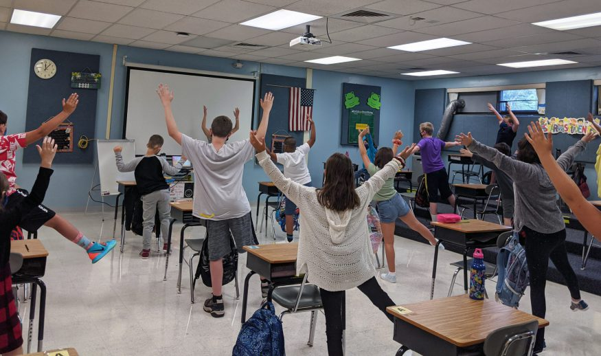 A photo of the backs of a class of WHBI students while they take a stretch break, with arms up, in class at their desks