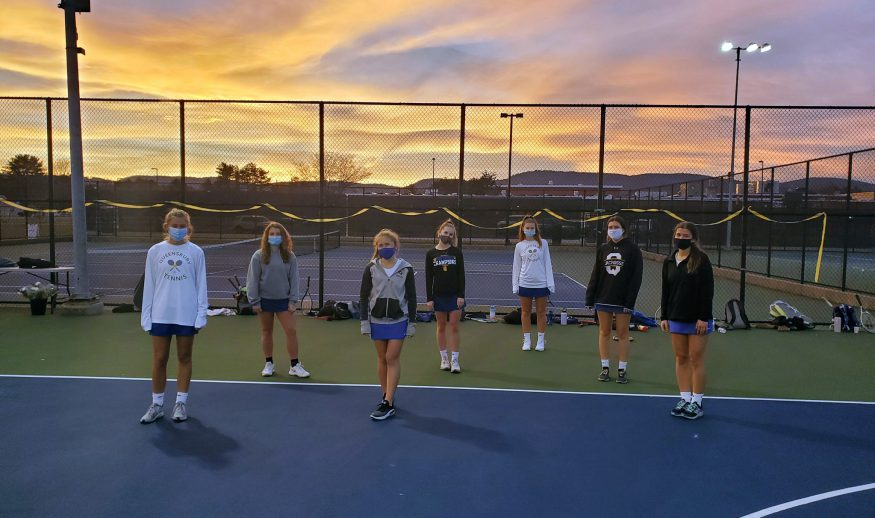 Six socially distanced girls tennis players pose on the tennis court in front a sunset
