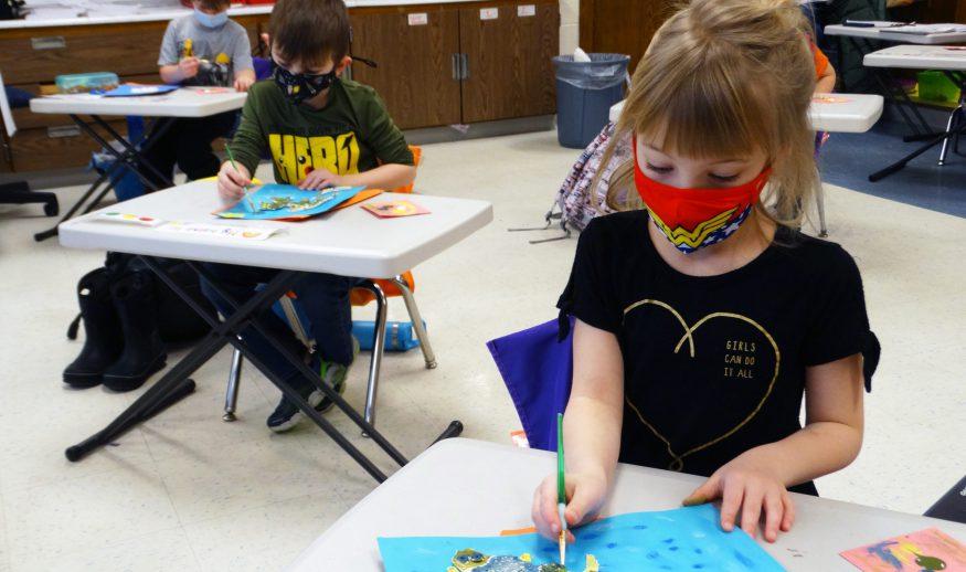 A masked female kindergartner works on a Monet inspired pond art project