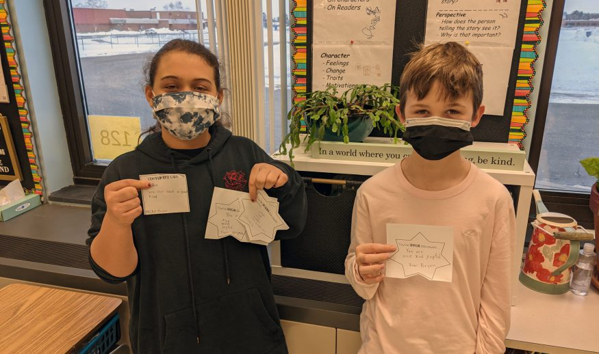 Two masked WHBI students, a girl on the left and a boy on the right, hold up pieces up paper that has a compliment written on it. Compliment is unreadable.