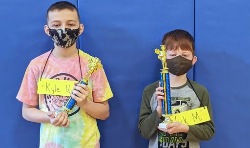 Two intermediate school boys pose with their spelling bee trophies