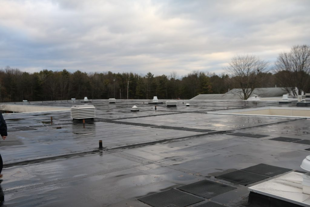 A photo taken on the roof of the elementary building showing parts of the roof that are old and need to be replaced